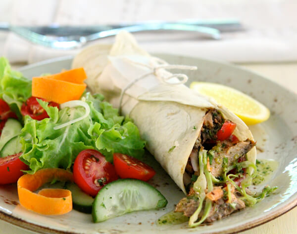 Lucky Star pilchard and black bean wrap with a tomato and red onion, coleslaw and fresh mint salad
